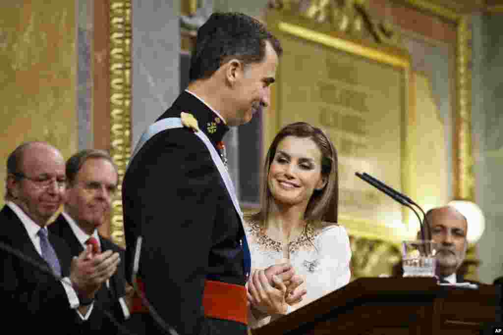 Spain's Queen Letizia holds the hands of her husband King Felipe VI during the swearing-in ceremony at the Spanish Parliament. Felipe is being formally proclaimed monarch after 76-year-old King Juan Carlos abdicated to enable younger royal blood to rally a country beset by economic problems, including an unemployment rate of 25 percent.