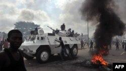 Xe chở binh sĩ gìn giữ hòa bình Liên Hiệp Quốc chạy ngang qua các ủng hộ viên của ông Alassane Ouattara trong lúc họ đốt lốp xe tại khu phố Abobo ở Abidjan