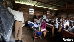 FILE - A teacher conducts a mathematics lesson to high school students in Democratic Republic of Congo town of Bunagana, Oct. 19, 2012. Many teachers are paid months late.