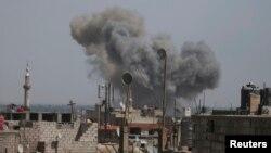 시리아 수도 다마스쿠스 외곽 반군 점령지역에서 24일 반군이 주장하는 정부군 공습으로 회색 연기가 피어오르고 있다.