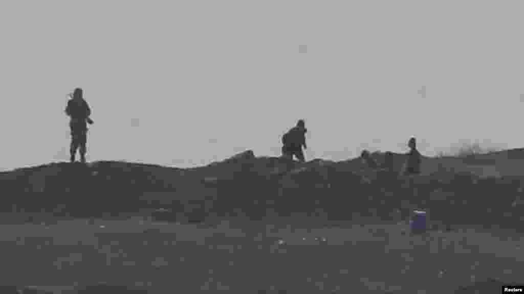 Des hommes armés, présumés être des combattants de l'Etat Islamiques par des sources locales, pris en photo au contrôle de passage à l'Ouest de la ville de Kobani, près de Mursitpinar à la frontière Turco-Syrienne, le 13 ocotbre 2014. REUTERS/Umit Bektas