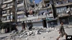 Cư dân đi ngang qua một tòa nhà bị phá hủy trong các vụ không kích ở Aleppo, Syria.