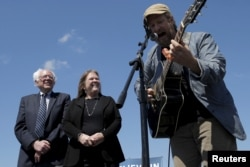 "U.S. Democratic presidential candidate Bernie Sanders and his wife, Jane, listen as Guy Forsyth performs ""This Land Is Your Land"" at a campaign rally in Austin, Texas, Feb. 27, 2016."