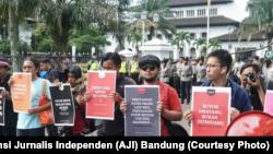 Sejumlah jurnalis mengangkat poster dalam aksi Hari Buruh di Bandung, 1 Mei 2019. Dalam aksinya, mereka menuntut kesejahteraan wartawan dan penghapusan kekerasan terhadap awak media. (Foto: Aliansi Jurnalis Independen (AJI) Bandung)