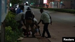 A wounded person is evacuated following an attack by gunmen on a restaurant in Ouagadougou, Burkina Faso, in this still frame taken from video August 13, 2017.