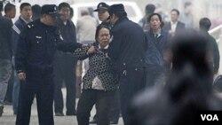 """Polisi Tiongkok mengusir seorang perempuan pendukung aktivis HAM yang tengah diadili di Beijing. Masyarakat Tiongkok mengecam banyaknya peningkatan kasus """"penghilangan paksa"""" oleh polisi Tiongkok (foto: dok)."""