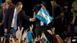 FILE - Ruling party presidential candidate Daniel Scioli holds an Argentine flag as he acknowledges supporters after primary elections in Buenos Aires, Argentina, Aug. 10, 2015.