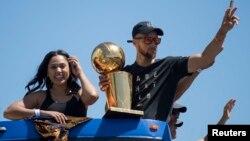 Stephen Curry (avec le trophée des champions NBA), sa femme Ayesha Curry, Oakland, Californie, le 15 juin 2017.
