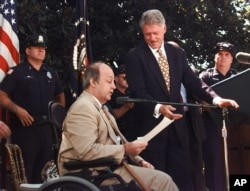 Former President Clinton gestures toward former White House press secretary James Brady in 1998 outside the White House, where he called on Congress to extend the Brady gun law.