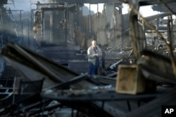 Dick Marsala looks through debris from his destroyed home after a wildfire roared through the Rancho Monserate Country Club Friday, Dec. 8, 2017, in Bonsall, Calif.