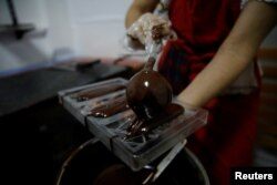 Adriana Pino makes chocolate bars at the +58 Cacao chocolate factory in Caracas, Venezuela, Oct. 6, 2017.