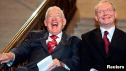 FILE - Northern Ireland's new first minister Ian Paisley (L) and deputy first minister Martin McGuinness smiling after being sworn in at a ceremony at Stormont, Belfast, Ireland, May 8, 2007.