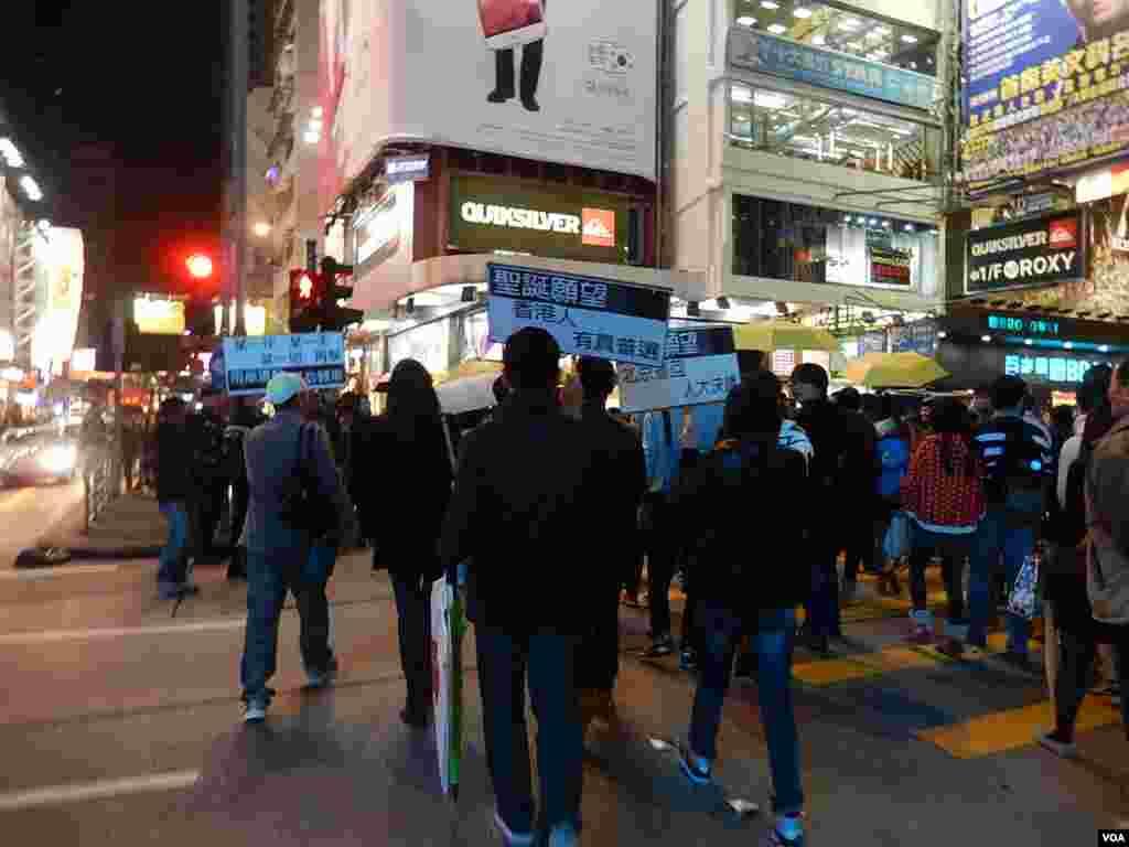 一批「購物團」人士手持標語在旺角街頭集體過馬路