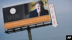FILE - A Trump Ocean Resort Baja billboard with a photo of Donald Trump advertises condos for sale on the outskirts of Tijuana, Mexico. But the Trump Ocean Resort Baja Mexico project collapsed, and dozens of buyers who lost their 30 percent deposits sued.
