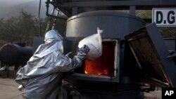 Seorang pekerja dengan mengenakan pakaian khusus anti api, tengah melemparkan sebuah tas berisi kokain ke mesin pembakaran di kantor pusat Kepolisian Nasional di Lima, Peru (6/6).