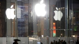 Pedestrians pass the Apple store location on Fifth Avenue in New York, June 6.