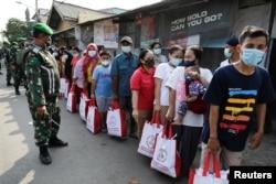 Warga mengenakan masker di tengah pandemi COVID-19, antre untuk menerima bantuan yang diberikan oleh Presiden Indonesia di Jakarta, 16 Juli 2021. (REUTERS/Willy Kurniawan/File Photo)
