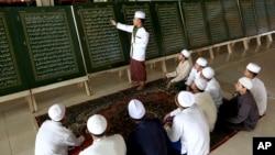 Seorang guru menjelaskan ayat-ayat Al-Qur'an yang dicetak pada pelat logam di kelas baca Al-Qur'an selama bulan Ramadhan di Pondok Pesantren Al-Ashriyyah Nurul Iman, Parung, Jawa Barat, Selasa, 6 Juni 2017. (Foto: dok).