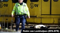 NETHERLANDS -- An armed policeman and a body (R) are seen at the scene where a shooting took place at the 24 Oktoberplace in Utrecht, March 18, 2019