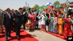 Chinese President Xi Jinping waves to children with Pakistan's Present Mamnoon Hussain, left, at Nur Khan airbase in Islamabad, Pakistan, April 20, 2015.