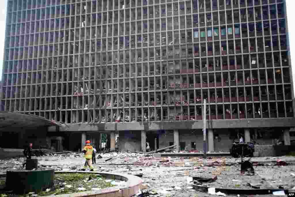 Ngày 22 tháng 7: Những đổ nát và mảnh vụn trên khắp khu vực bên ngoài tòa nhà ở trung tâm Oslo, sau khi một vụ nổ phá hủy nhiều tòa nhà, kể cả văn phòng thủ tướng Na-Uy, làm vỡ các cửa kiếng, làm giấy tờ tài liệu vương vải đầy đường. (AP Photo / Fartein R