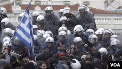 Polisi anti huru-hara menghalang-halangi demonstran yang berusaha masuk ke gedung Parlemen Yunani di Athena (7/2).