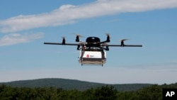 FILE - A prototype drone is seen carrying a parcel for delivery.