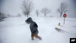 Cassie Peterson camina entre la nieve durante la más reciente tormenta invernal en Portland, Maine, el martes, 13 de marzo de 2018.