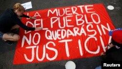 Manifestantes muestran un cartel que clama por justicia durante una protesta contra el gobierno.