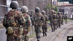 Liberian soldiers walk through streets to prevent panic as fears of the deadly Ebola virus spread in the city of Monrovia, Liberia, Friday, Aug 1, 2014. U.S. health officials warned Americans not to travel to the three West African countries hit by the wo