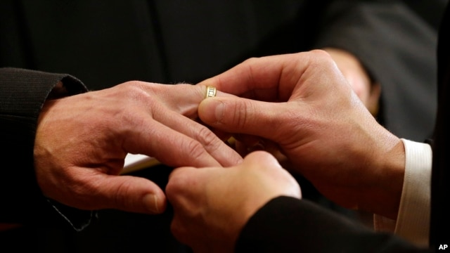 Same-sex couple exchange wedding band, (File photo).