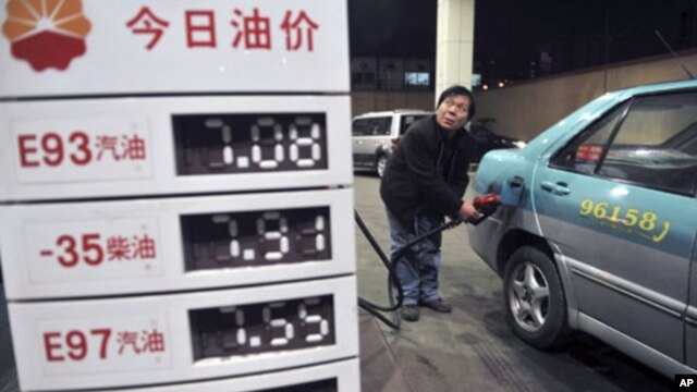 A taxi driver looks at the price as he fills the tank of his car near a board showing recently increased prices at a gas station in Shenyang, Liaoning province, February 20, 2011.