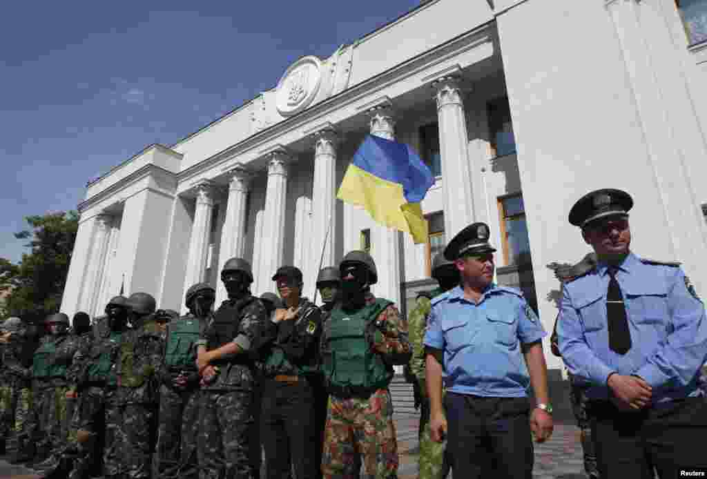 Volunteers from the Donbass battalion and Maidan self-defense group stand guard with official security guards outside the Ukrainian parliament in Kyiv, July 3, 2014.
