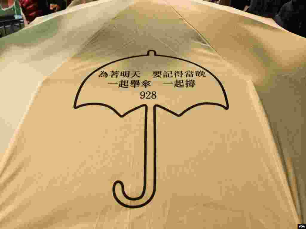 有香港市民撑着印有雨伞运动标志的黄色雨伞,参加平安夜游行