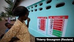Seorang perempuan dan anak-anak melihat poster-poster pencegahan Ebola di sebuah sekolah Toulepleu di barat Pantai Gading, 4 November 2014. (Foto: Thierry Gouegnon/Reuters)