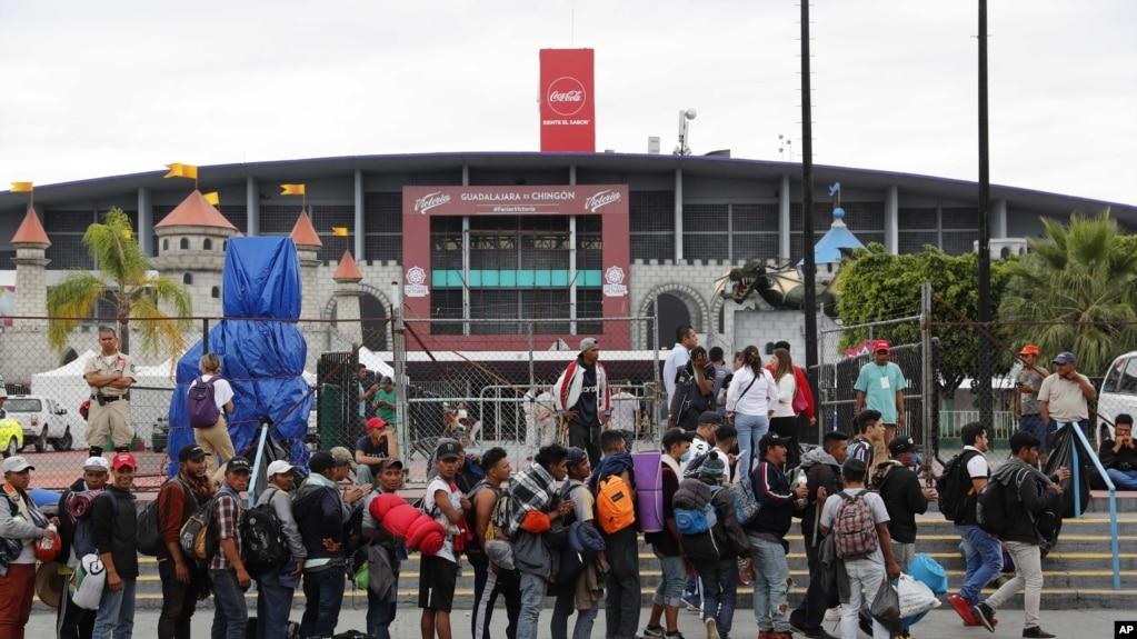 Migrantes hacen fila para ingresar al Auditorio Benito Juárez, en Guadalajara, México.