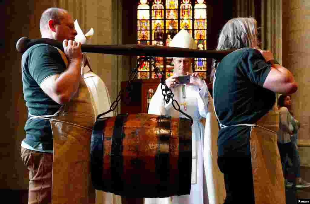 Bearers carry a barrel of beer ahead of a mass celebrating Saint-Arnould, patron saint of brewers, at Saint Gudula Cathedral in Brussels, Belgium.