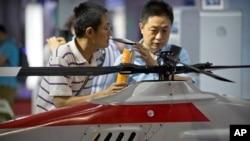 Para pengunjung memperhatikan helikopter drone di sebuah pameran di Beijing, China, 18 Mei 2018.