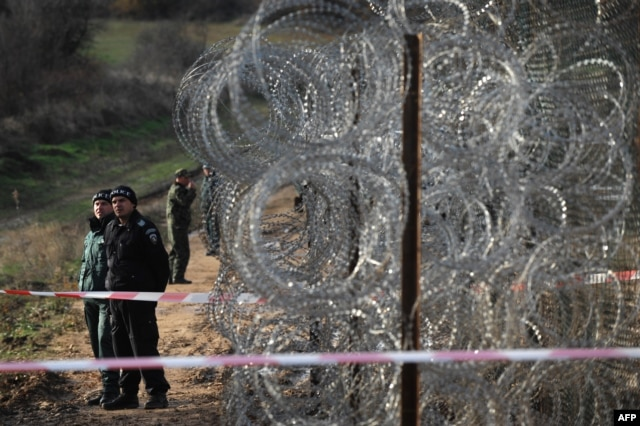 Border police stand guard next to a border fences which are planned to be built on the Bulgarian border with Turkey, near the village of Golyam Dervent on November 28, 2013. AFP PHOTO / NIKOLAY DOYCHINOV