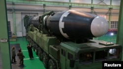 North Korea's leader Kim Jong Un appears near the newly developed intercontinental ballistic rocket called the Hwasong-15 in this undated photo released by North Korea's Korean Central News Agency (KCNA).
