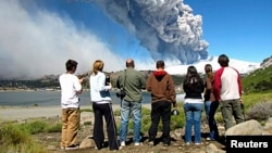 FILE - Local residents watch a column of smoke and ash rise from the Copahue volcano, located on the Chile-Argentina border, December 22, 2012.