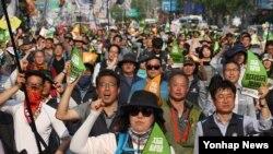 1일 오후 2017 세계 노동절 대회 참가자들이 '지금당장 최저임금 1만원'이라고 적힌 손 팻말을 든 채 서울 종로에서 광화문 쪽으로 행진하고 있다.