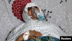 FILE - A woman breathes through an oxygen mask at al-Quds hospital, after a hospital and a civil defense group said a gas, what they believed to be chlorine, was dropped alongside barrel bombs on a neighborhood in Aleppo, Syria, Aug. 11, 2016.