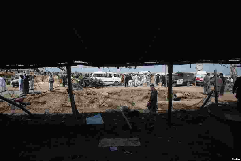 Security officials, residents and media personnel gather at the site of a bomb attack in Jalozai camp in Nowshera district, northwestern Pakistan, March 21, 2013.