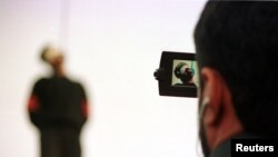 FILE - A police cameraman takes video footage of the hanging of a convicted murderer at Jamshidieh park in Tehran, Oct. 27, 2002.