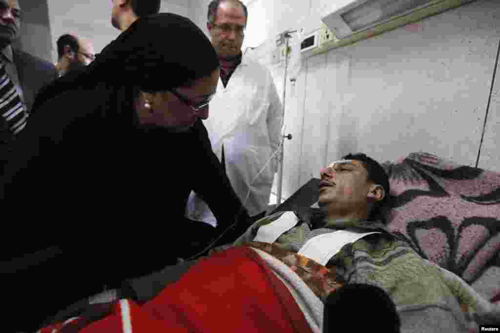 Dr. Maha Rabat, Minister of Health and Population, speaks to an injured man receiving medical treatment at a hospital after an explosion outside the police headquarters in Mansoura, Dec. 24, 2013.
