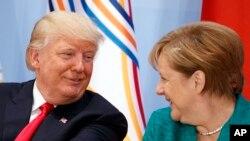 트럼프 대통령이 8일 G20 정상회의 여성기업가 지원 회의에서 앙겔라 메르켈 독일 총리와 담소를 나누고 있다.