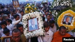 Thousands of mourners gather at the gates of the Royal Palace minutes after the coffin of former king Norodom Sihanouk arrived in Phnom Penh October 17, 2012.