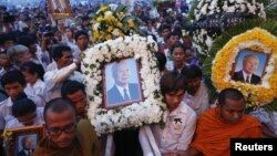 Thousands of mourners gather at the gates of the Royal Palace minutes after the coffin of former king Norodom Sihanouk arrived in Phnom Penh October 17, 2012. Tens of thousands poured into Cambodia's capital to witness the procession on Wednesday.