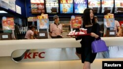 A woman holds food inside a KFC restaurant in Beijing, May 9, 2013. Yum Brands Inc, the largest foreign fast-food chain in China, is strengthening its media strategy in the country in a bid to win back customer loyalty after a series of food scares that